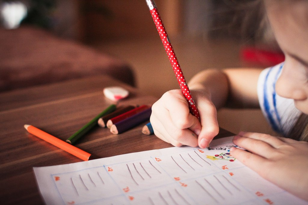 Little Girl Writing on a Paper with a Pencil