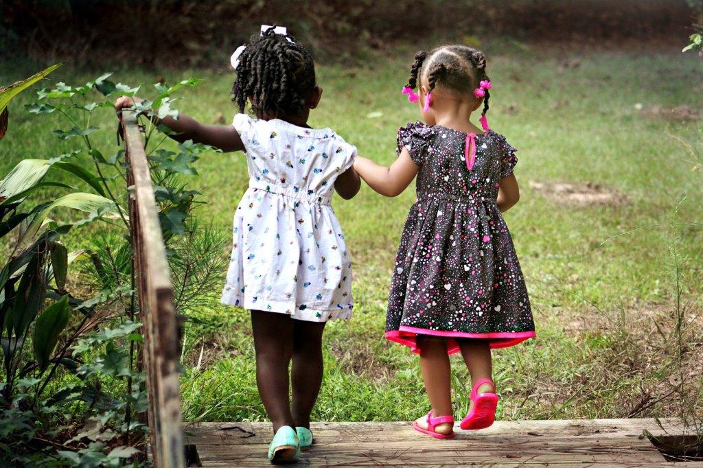 Two Little Black Girls Walking in the Yard