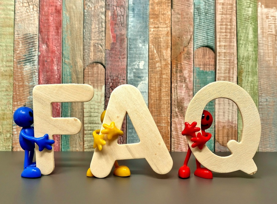 Wooden letters FAQ are held, frequently asked questions for AB Education Copy
